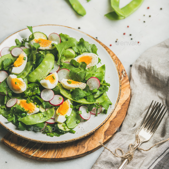 Green salad with radish, boiled egg, arugula, green pea, mint - Stock Photo - Images