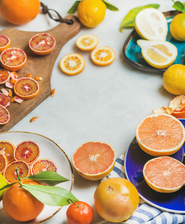 Natural fresh citrus fruits in ceramic plates over grey background - Stock Photo - Images