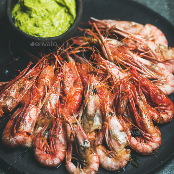 Roasted red shrimps with guacamole avocado sauce in black plate - Stock Photo - Images