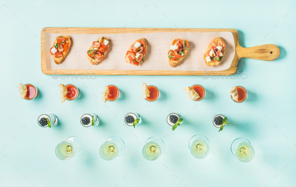 Snacks, brushettas, gazpacho shots, desserts, champagne over pastel blue background - Stock Photo - Images