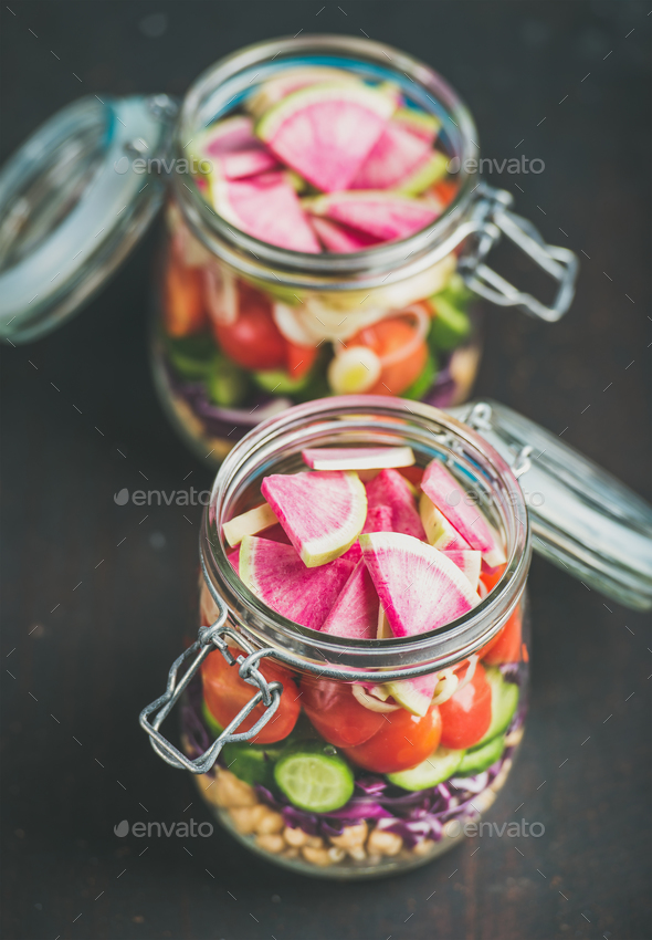 Vegetable, chickpea sprout salad in jars, dark scorched wooden background - Stock Photo - Images