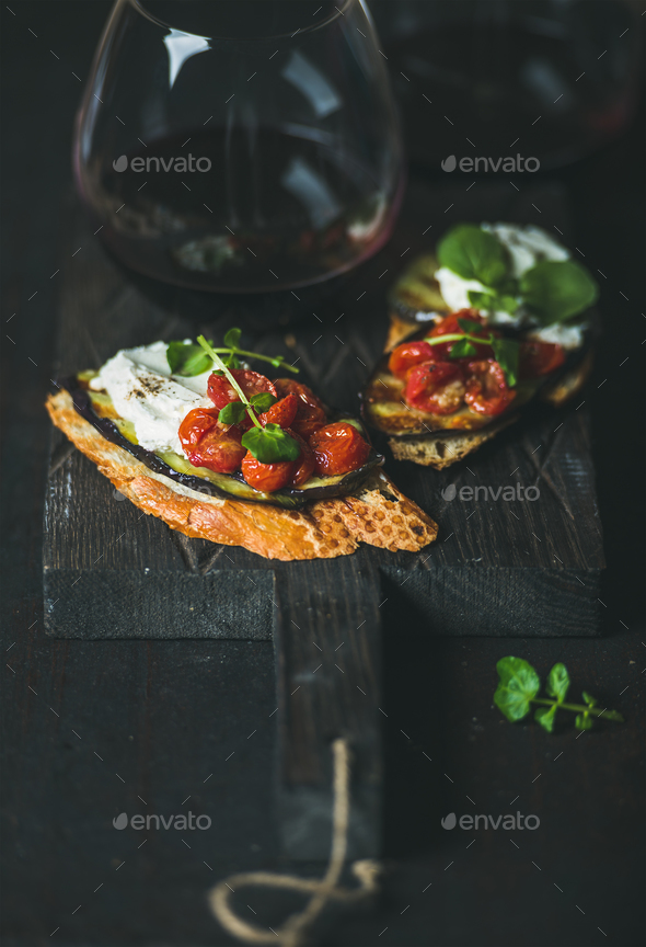 Red wine in glass and brushetta with vegetables, cream-cheese, arugula - Stock Photo - Images