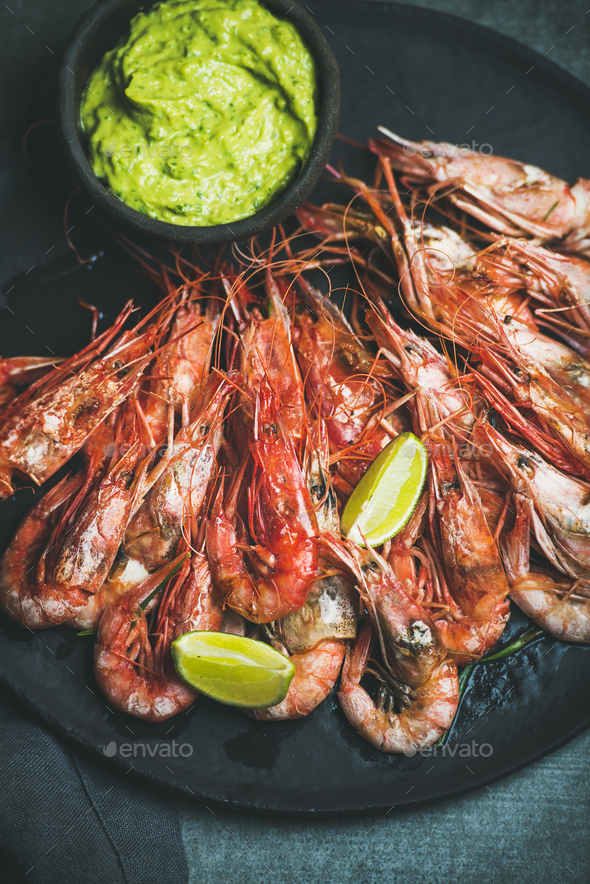 Roasted red shrimps with guacamole avocado sauce and lemon slices - Stock Photo - Images