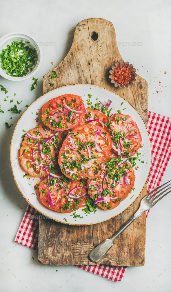 Fresh tomato, parsley and onion salad on shabby wooden board - Stock Photo - Images