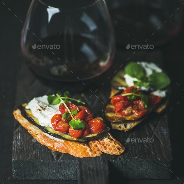 Wine, brushetta with eggplant, tomatoes, garlic, cream-cheese and arugula - Stock Photo - Images