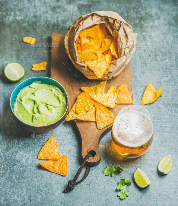 Mexican corn chips, fresh guacamole sauce and beer, concrete background - Stock Photo - Images