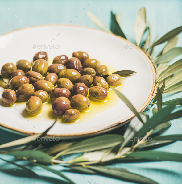 Pickled olives on plate and olive-tree branch over blue background - Stock Photo - Images