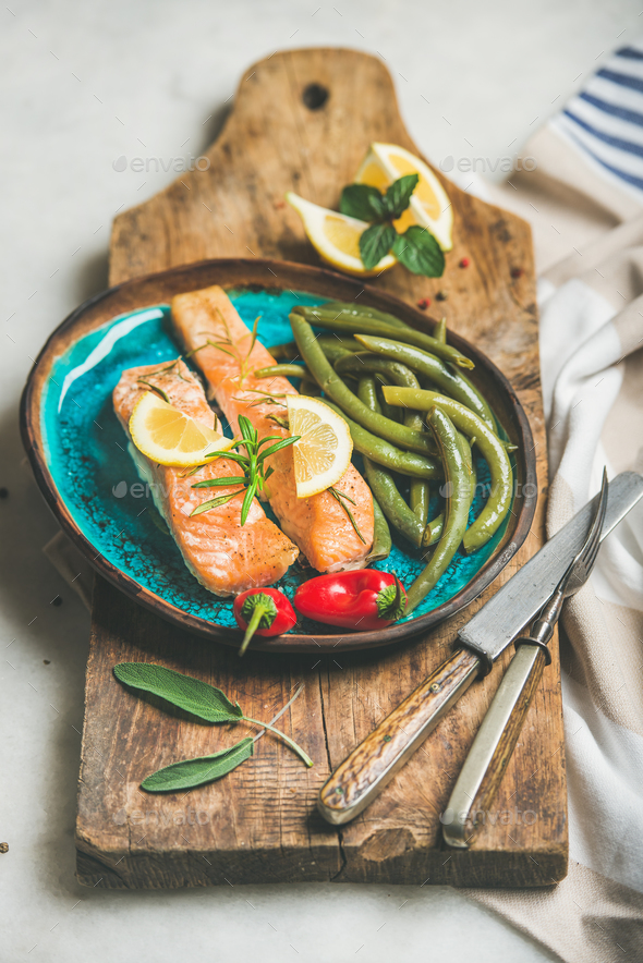 Roasted salmon fish with lemon, rosemary, chilli pepper, poached beans - Stock Photo - Images