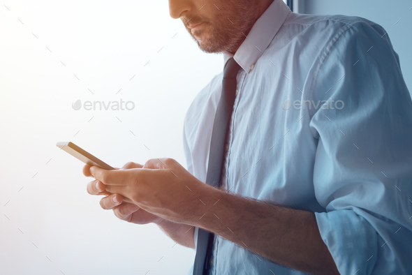 Businessman standing next to office window and texting - Stock Photo - Images