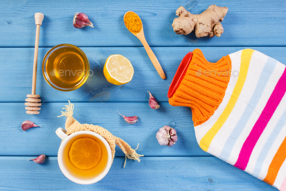 Hot water bottle, cup of tea and ingredients for preparation warming beverage for autumn or winter - Stock Photo - Images
