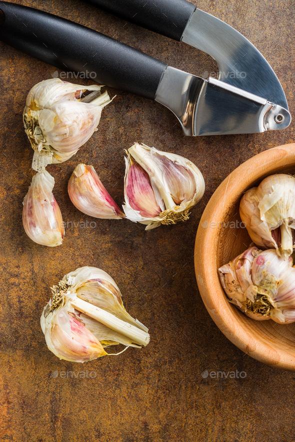 Fresh garlic and garlic presser. - Stock Photo - Images