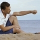 Young Man Spreads Sand Through Your Fingers on the Beach - VideoHive Item for Sale