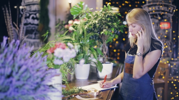 VideoHive Female Florist on the Phone Orders Flowers From the Supplier 20835808