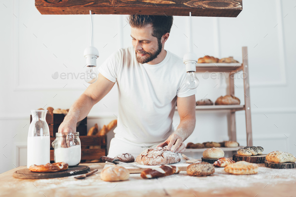 Baker with a variety of delicious freshly baked bread and pastry - Stock Photo - Images