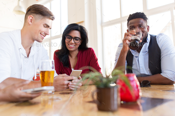 happy friends with smartphone drinking beer at bar - Stock Photo - Images
