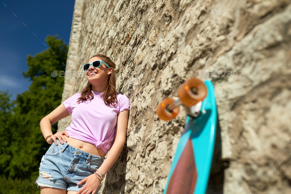 happy teenage girl in shades with longboard - Stock Photo - Images