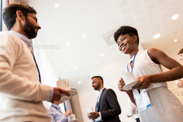 business people with conference badges and coffee - Stock Photo - Images