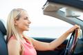 happy young woman driving convertible car