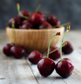 Red cherries in a bowl on a old wooden background