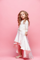 Full length of beautiful little girl in dress standing and posing over white background