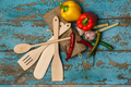 Wooden cutlery and different vegetables on shabby blue backgroun
