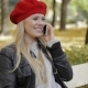 Pretty Woman in Beret Speaking on Phone