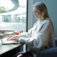 Woman in Comfortable Armchair Using Laptop