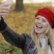 Happy Woman Taking Selfie in Park