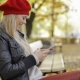 Happy-looking Woman in Beret Using Smartphone - VideoHive Item for Sale