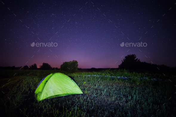 Green tent under the starry sky in the field - Stock Photo - Images