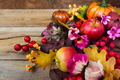 Fall decoration with red berries, rowan leaves, apples, pink flo