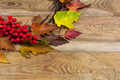 Thanksgiving wreath with leaves and rowan berries on wooden back