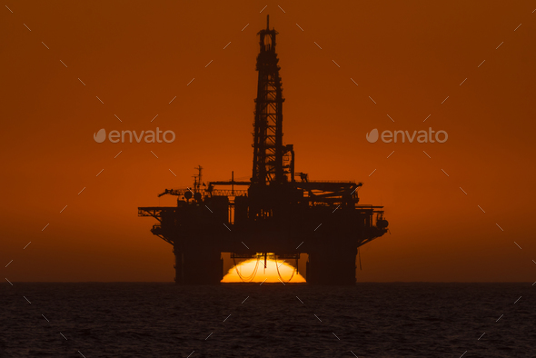 Sun setting behind oil drilling platform at Longbeach in Namibia - Stock Photo - Images