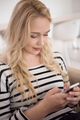 woman sitting on sofa with mobile phone - PhotoDune Item for Sale