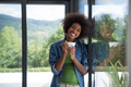 African American woman drinking coffee looking out the window - PhotoDune Item for Sale