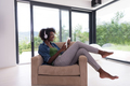 African american woman at home in chair with tablet and head pho - PhotoDune Item for Sale