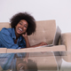 African American woman using laptop on sofa - PhotoDune Item for Sale