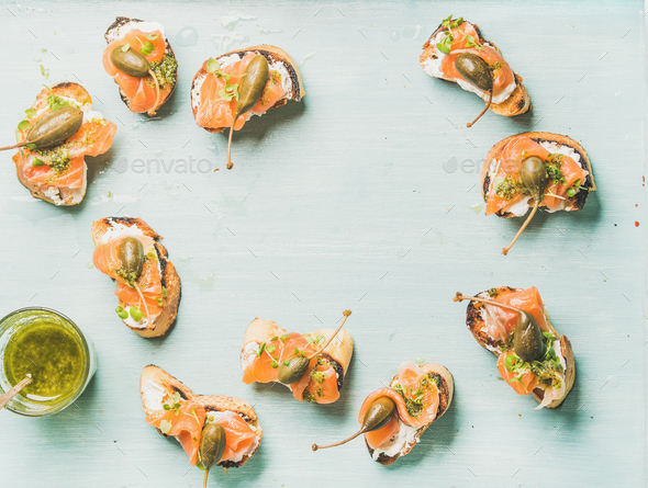 Crostini with smocked salmon, pesto sauce in glass, watercress, capers - Stock Photo - Images