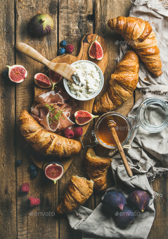 Croissants, ricotta cheese, figs, fresh berries, prosciutto and honey - Stock Photo - Images