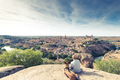 TRaveller man and dog watching Toledo cityscape from hill