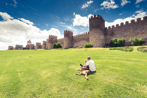 Man laying on grass with dog by city Avila,Spain - Stock Photo - Images