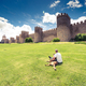 Man laying on grass with dog by city Avila,Spain - PhotoDune Item for Sale