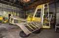 The partially-built airplane in a dark industrial building at night