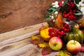 Fall enterpiece with rowan berries, green pumpkin, oak leaves an