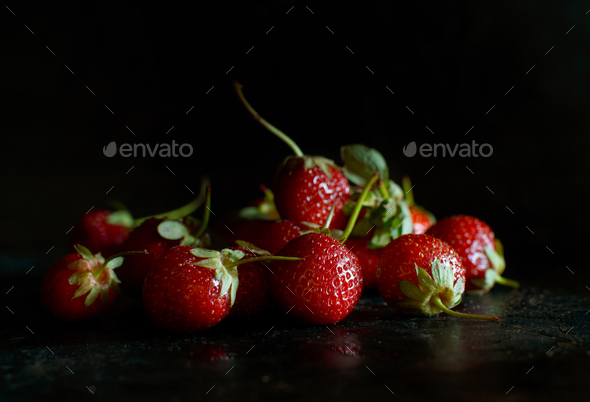Strawberries in a tray on a dark table - Stock Photo - Images