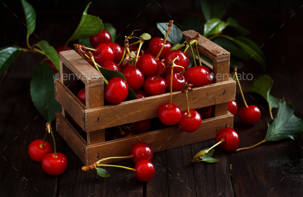 Fresh sour cherries in a box on a wooden table - Stock Photo - Images