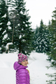 Woman walking in winter forest on snowy trail