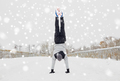 young man doing handstand in winter