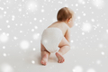 little baby in diaper crawling on white floor