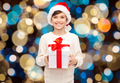 smiling happy boy in santa hat with christmas gift
